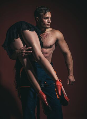 Young sexy couple. Hot Firefighter. Muscular man. We need to live with passion. Hot sexy Firefighter. Firefighter hot and sexy. Couple on dark red background. Young sexy couple.