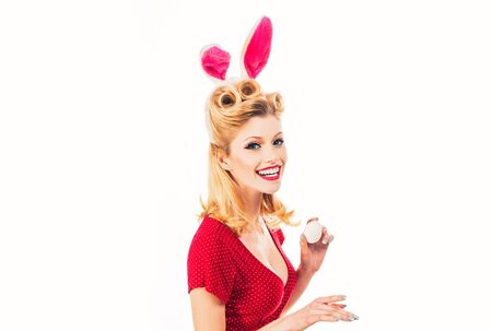 Happy woman preparing for Easter. Beautiful blonde girl with bunny ears and Easter egg. Pretty girl hunts for Easter eggs. Lovely woman in rabbit costume. Hand with color Easter eggs.