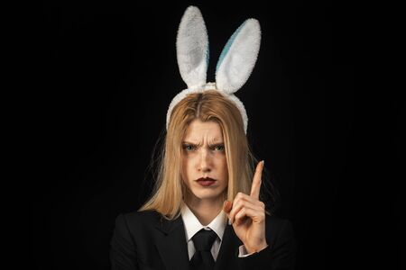 Sexy blonde girl with lace bunny ears. Sexy model dressed in costume Easter bunny. Beautiful young woman with bunny ears and blank poster on black background isolated.
