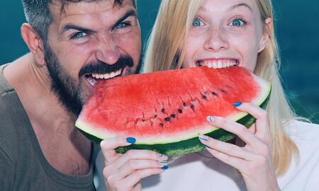 Happy carefree couple eat watermelon. Vitamins and healthy concept. Enjoying a watermelon. Couple friends eating a watermelon slice and laughing together. Holiday. Imagens