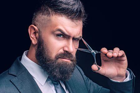 Schere-Konzept. Bärtiger Mann, bärtiger Hipster. Stilvoller Männerbart. Friseurschere. Vintage Friseursalon, Rasieren. Langer Bart, kaukasischer Hipster mit Schnurrbart.