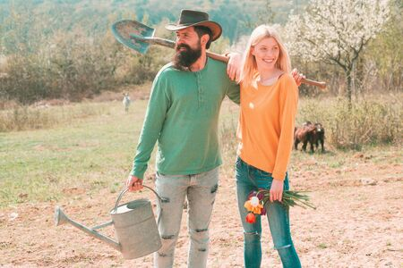 Lifestyle and family life. Eco living. A farmer and his wife standing in their field. Two people gardening in the backyard garden. Smile Couple on farmland.