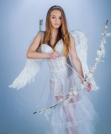 Cute little female cupid shoots a bow. Angel children girl with white wings. Innocent Girl with angel wings standing with bow and arrow against white background isolated. Innocent girl.