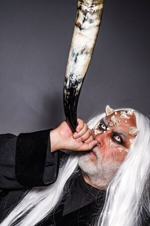 Wizard demon man with dragon skin and horns. Bearded old man dressed like Halloween monster. Devil horns. Horror with scary Halloween man. Vampire man with white eyes Фото со стока