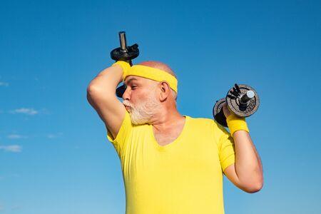 Wie Sport und Muskeln. Porträt des gesunden glücklichen Seniors. Älterer Mann in seinen Siebzigern trainiert und hebt wiegen. Muskelstarkes Kraftkonzept.