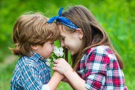 Kids girl and boy blowing dandelion flower in green meadow outdoor.