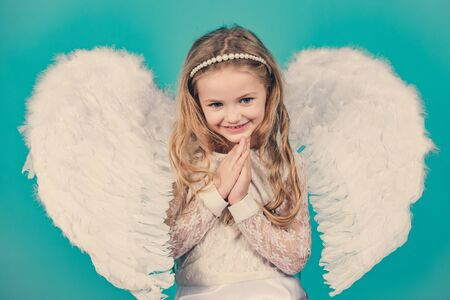 Beautiful little angel girl. Mischievous little angel girl standing with your clenched fists. Beautiful little angel girl standing with your arms close to your chest as in prayer.