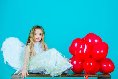 Kids Valentines Day. Wonderful blonde little girl in the image of an angel with white wings. Beautiful young girl wearing angel wings. Child angel with a beautiful wings.