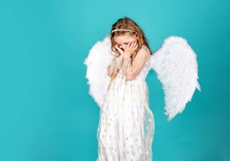 Face of beautiful little angel girl on color background. Pretty little angel girl. Child with angelic face.