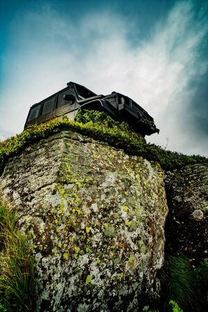 Truck car wheel on offroad steppe adventure trail. SUV race on dirt. Low angle view of front of SUV on mountain road. 스톡 콘텐츠