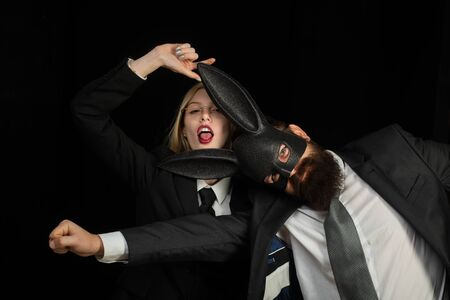 Couple woman in rabbit costumes and man in suit. Lovers are fooling around. Handsome man with beard in playboy mask. Bearded man. Beautiful woman in glasses.