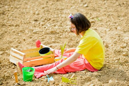 Kid portrait on farmland. I like spending time on farm. Child girl having fun with little shovel and plant in pot.