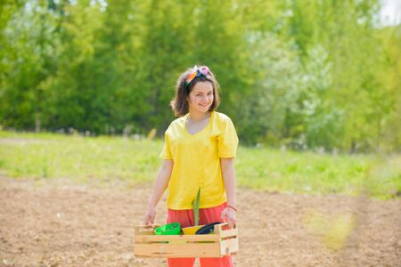 Children summer activities. Happy kids work plant and water in green spring garden. Stockfoto