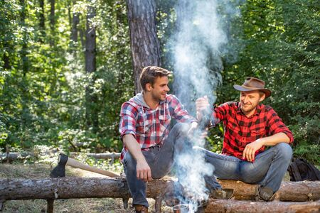 Friends relaxing near campfire after day hiking or gathering mushrooms. Company two male friends enjoy relaxing together in forest. Two friends guy camping in forest.