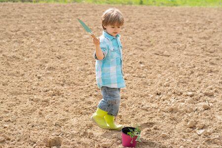 I like spending time on farm. Spring gardening routine. Child play in spring garden. Portrait of kid gardener carrying harvested in farm.