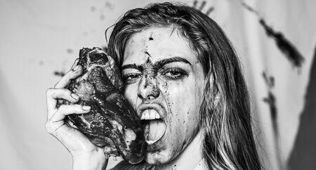 Concetto di bistecca. Donna affamata con bistecca di carne. Donna arrabbiata emotiva affamata che grida. Una donna sensuale sanguinosa vuole mangiare. Facce affamate e arrabbiate. Una pazza storia dell'orrore. Cucina sexy e bistecca succosa.