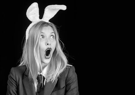 Bunny woman. Happy easter. Portrait of a happy woman in bunny ears winking. Easter bunny woman. Sexy woman with mask Easter bunny on a black background and looks very sensually.