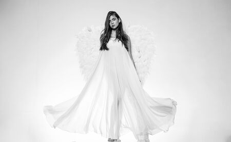 Romantic young beauty as an angel. Valentines Day symbol. Long white wings. Valentines day and costumes concept.