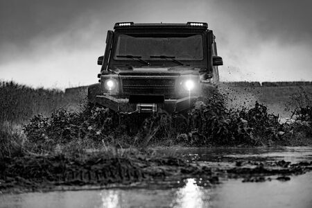 Water splash in off-road racing. Beautiful nature. Classic 4x4 car crossing water with splashes on muddy road. Offroad car on bad road.
