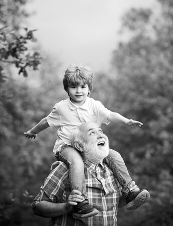 Grandfather and his grandson playing outdoors. Family holiday and togetherness. Generation. Grandfather and grandson in the park. Foto de archivo