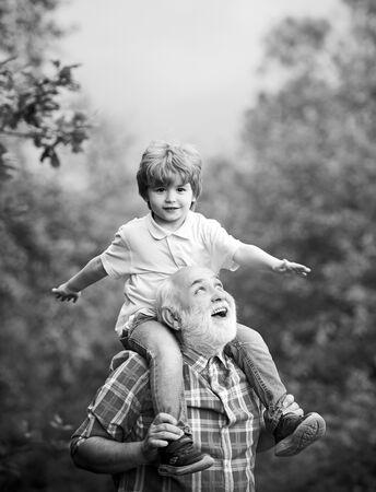 Großvater und sein Enkel spielen im Freien. Familienurlaub und Zweisamkeit. Generation. Großvater und Enkel im Park. Standard-Bild
