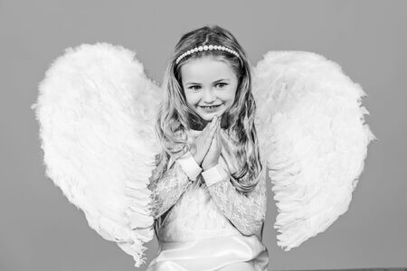 Valentines Day. Angel. Mischievous little angel girl standing with your clenched fists. Angels little hands crossed for you.