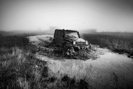 Wheel close up in a countryside landscape with a muddy road. Off-road vehicle stuck on impenetrable road after rain in the countryside. 스톡 콘텐츠