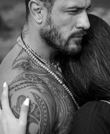 Donna sexy e in forma e uomo bello che abbraccia con il tatuaggio. Passione e tocco sensuale. La giovane coppia innamorata si abbraccia. Romantico e amore.