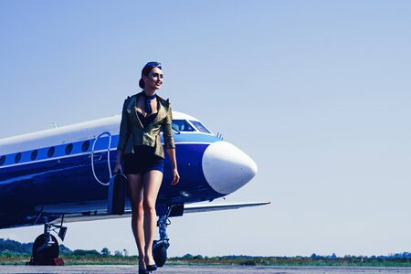 Charming stewardess dressed in blue uniform. Beautiful stewardess. Traveling and jet plane flying concept. Journey and jet trip. Air stewardess. Flying attendants air hostess.