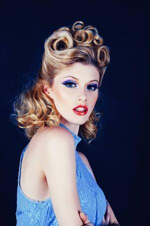 Stijlvol studioportret van een mooie jonge vrouw. Sluit omhoog dame. Mooie blonde vrouw in blauwe jurk. Pin-up stijl make-up. Luxe make-up. Blije meid. Mooie blonde vrouw met retro kapsel.