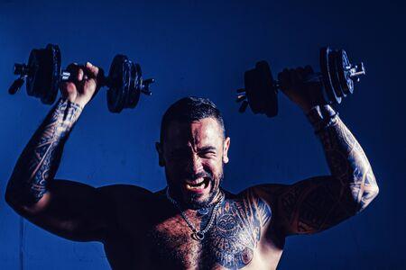 Chico joven culturista muscular haciendo ejercicios con pesas sobre fondo oscuro. Entrenamiento intenso.
