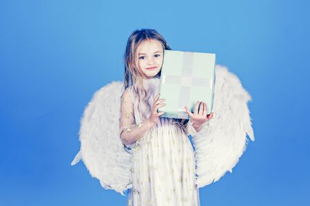 Wonderful blonde little girl in the image of an angel with white wings. Little angel Girl in white dress with angel wings on isolated background. Фото со стока