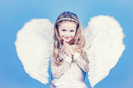 Angels little hands crossed for you. Mischievous little angel girl standing with your clenched fists.