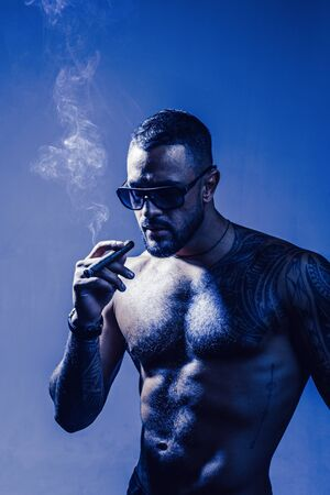Expensive tobacco. Cigar smoking enjoy life moment. Bearded muscular macho beautiful torso fashion sunglasses smoking cigar. Elite tobacco. Pure enjoyment. Consuming tobacco. Tattooed man with cigar Foto de archivo