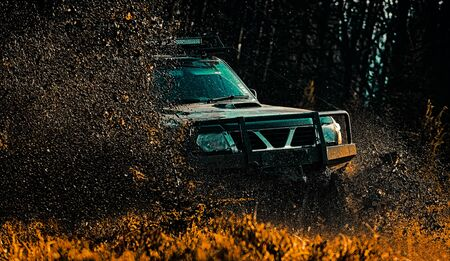 Mud and water splash in off-road racing. Drag racing car burns rubber. Extreme. Off-road car. Tracks on a muddy field. Offroad vehicle coming out of a mud hole hazard. Expedition offroader.