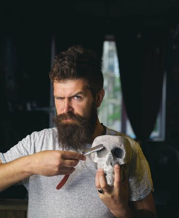 Friseurschere. Rasiercreme aus Sandelholz. Friseurschere und Rasiermesser. Ideen über Barbershop und Friseursalon. Rasieren im Vintage-Friseursalon. Friseur macht Frisur zu einem Mann mit Bart.