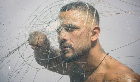 Sexy hispanischer tätowierter Mann hinter Glasscherben. Einschussloch im Glas. Zerstörungs- und Quetschtestkonzept. Mann Stil. Macho-Mann-Glasschneider hinter zerbrochenem Glas.