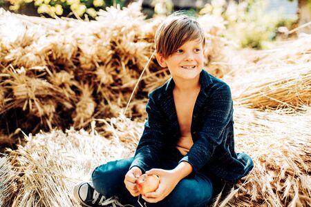 Fair-haired boy lies on hay background and eats an apple. Sale for entire autumn collection, incredible discounts and wonderful choice. Bye summer - hi autumn. Back to school.