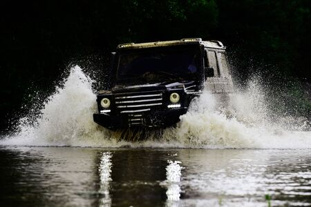 Mud and water splash in off-road racing. Expedition offroader. Drag racing car burns rubber. Extreme. Off-road car.