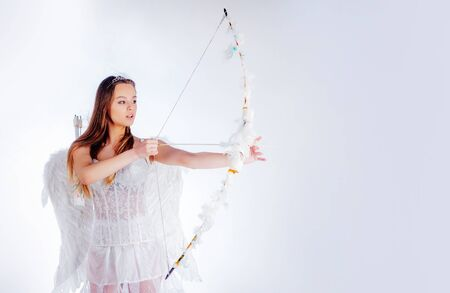 Sweet girl wearing angel costume white dress and feather wings. Cupid in valentine day. Valentines day cupid. Teen angel. Enjoying magic moment. Angel children girl with white wings.