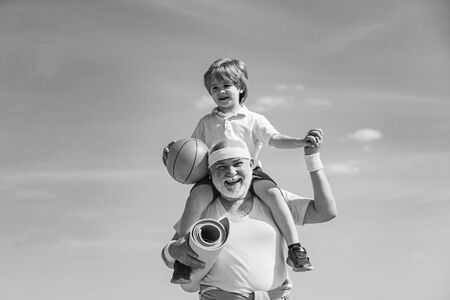 Grandpa and grandson spotting. Father and child training together. I love sport. Active family enjoy sport and fitness. Happy loving family.