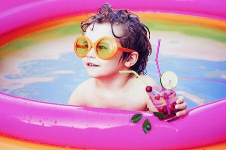 在游泳池里享受。孩子们学习游泳。小男孩在度假村的游泳池放松和喝鸡尾酒。时尚太阳镜。
