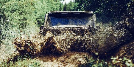 Off road sport truck between mountains landscape. Offroad vehicle coming out of a mud hole hazard. Drag racing car burns rubber. Extreme. Jeep crashed into a puddle and picked up a spray of dirt.