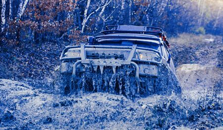 4x4 travel trekking. Track on mud. Off-road vehicle goes on the mountain. Mud and water splash in off road racing. Safari. Offroad. Adventure travel. Off-road travel on mountain road. Offroad vehicle coming out of a mud hole hazard. Stock fotó
