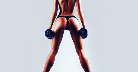 Frau mit schönem Körper. Gesunder Lebensstil. Sportliches Mädchen in der Turnhalle. Frau Fitness-Konzept. Hintern und Hanteln. Banner für Kopienraumtext.