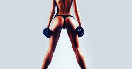 Woman with beautiful body. Healthy lifestyle. Sporty girl in the gym. Woman fitness concept. Butt and dumbbells. Banner for copy space text.