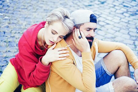 Enjoying music. Youth just want have fun. Freedom feeling. Youth fashion. Feeling free and stylish. Man and woman modern clothes for youth relaxing outdoors. Forever young. Couple hang out together