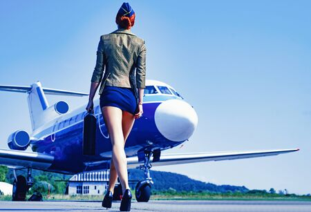 Profession stewardess. Air hostess. Female flight attendant. Air stewardess. Travel concept. Commercial airplane flying with beautiful charming stewardess. Fly plane and stewardess attendant concept.