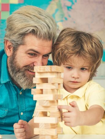 Father and son playing stacking wood blocks Jenga games for meditation practice. Children building wood blocks at home