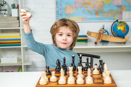 Thinking child. Little boy playing chess. Concentrated boy developing chess strategy, playing board game.